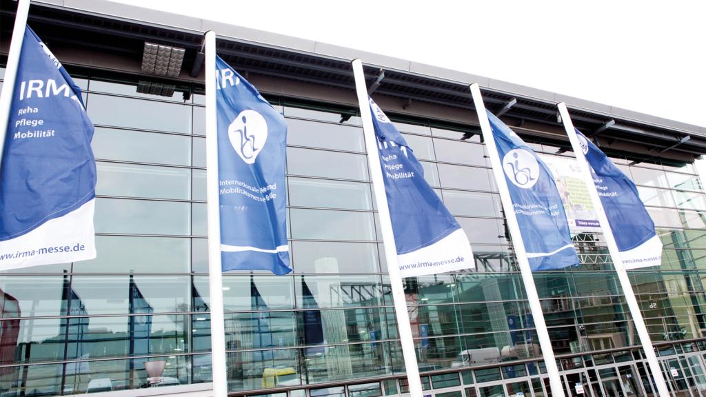 Messegebäude der IRMA-Reisemesse mit wehenden Fahnen