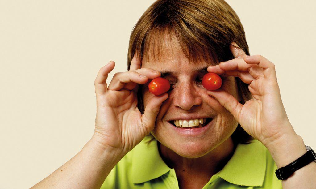 Frau hält sich zwei Tomaten vor die Augen