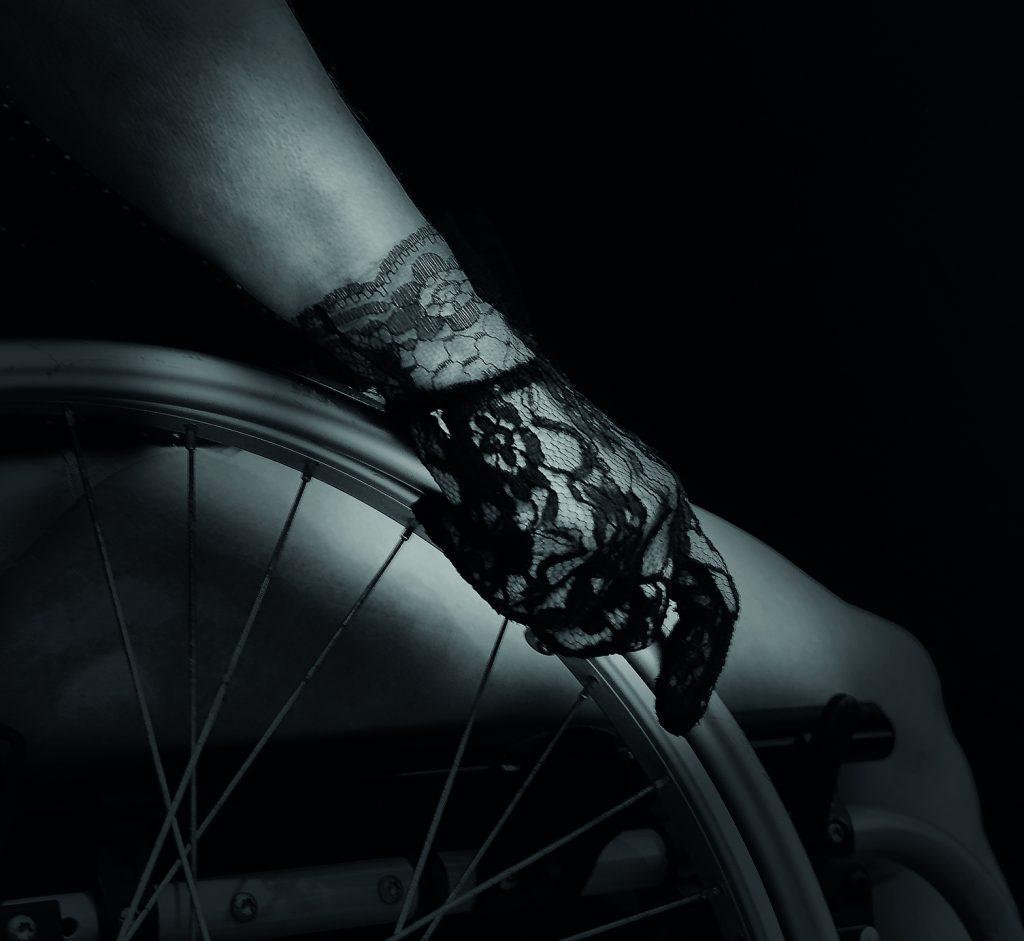 SW-Netzhandschuh auf Rollstuhl-Rad aufliegend