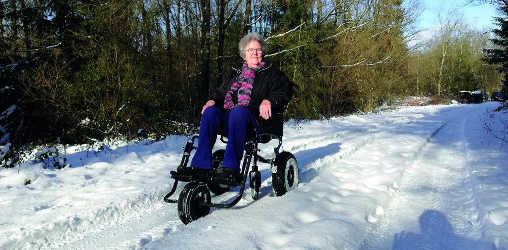 Frau in umgebauten Rollstuhl im Schnee