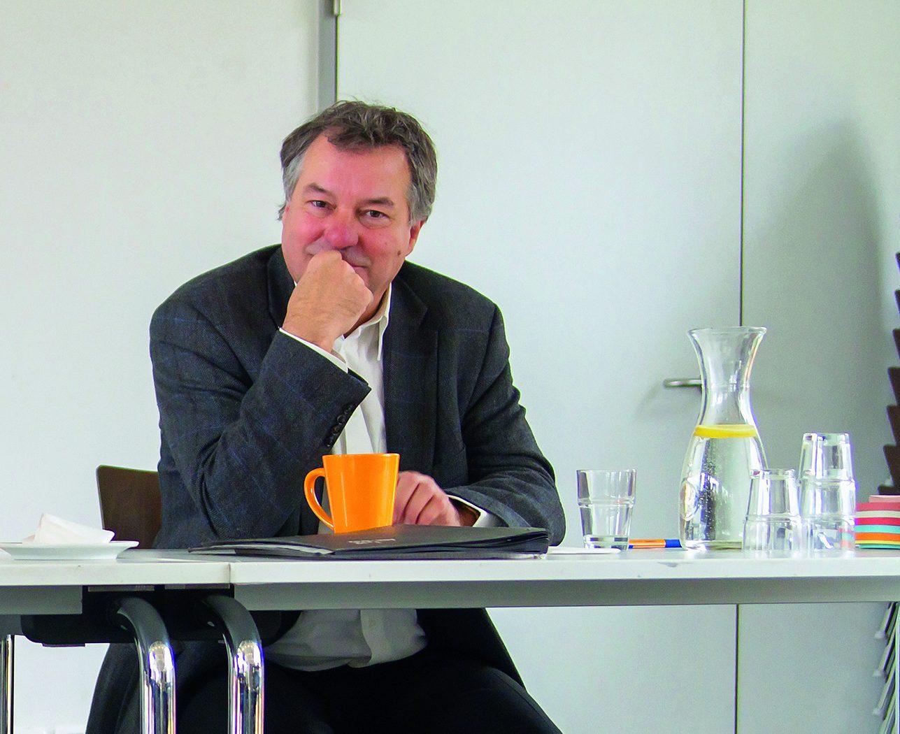 Mann sitzt af Stuhl im Office-Environment